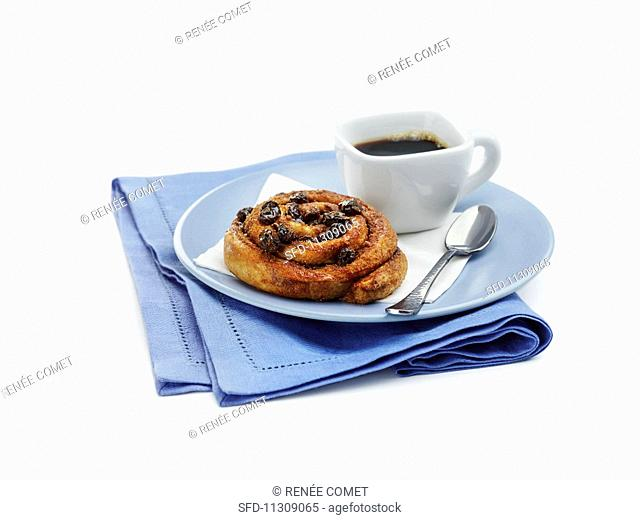 A wholemeal cinnamon bun with raisins served with coffee