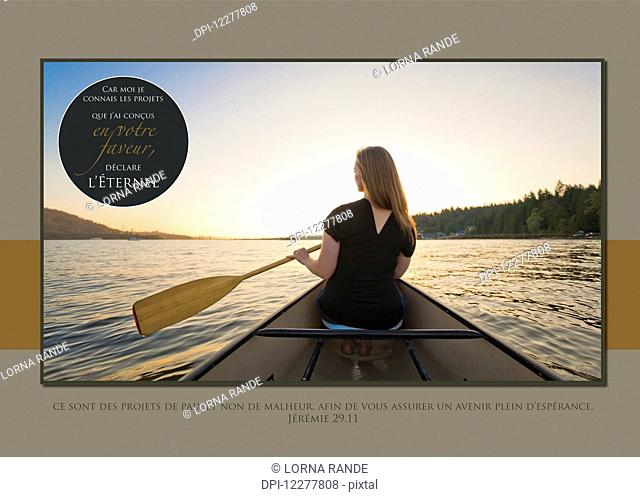 A young woman rowing in a boat at sunset with french scripture; Vancouver, British Columbia, Canada