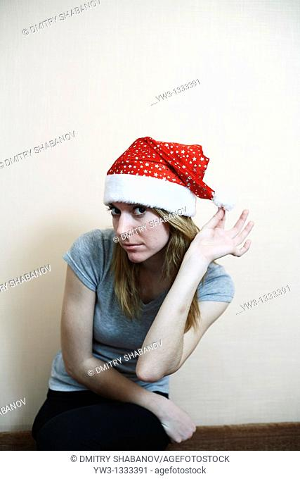 pretty girl in the Christmas hat against light wall posing