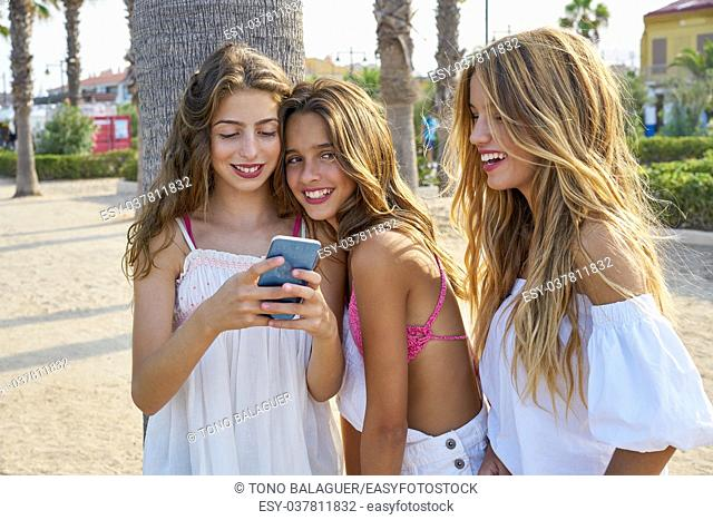 Teen best friends girls group playing with smartphone in palm trees beach