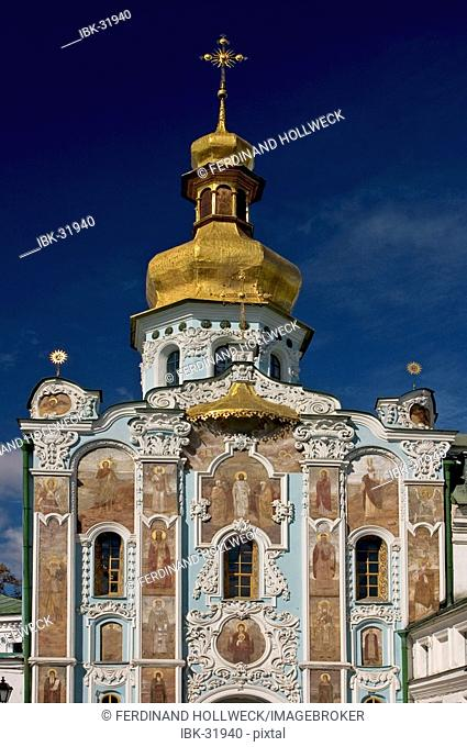 Ukraine Kiev the monastery of cave Kyjevo Pecers'ka Lavra view to the Trinity gate church blue sky and clouds shining dome and cross of church wall paintings...