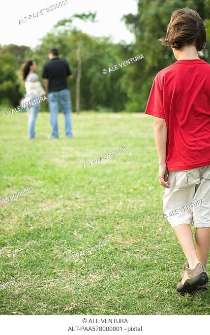 Boy walking sulkily toward parents having conversation distance