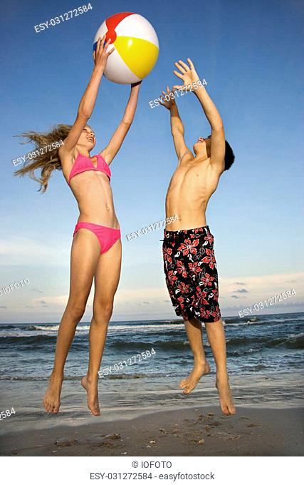 Caucasian pre-teen girl and boy playing with beachball on beach