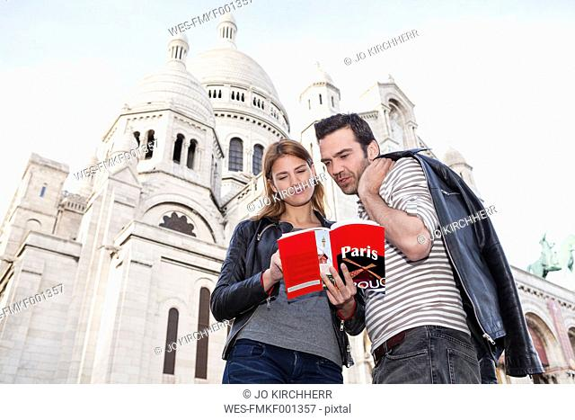 France, Paris, portrait of couple with travel guide in front of Sacre Coeur