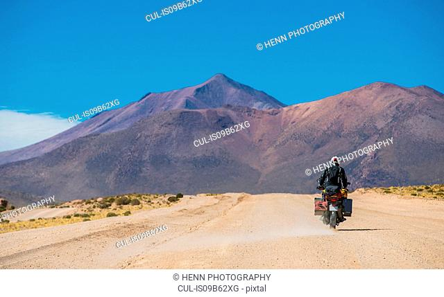 Motorcyclist riding motorcycle on dusty road, Uyuni, Oruro, Bolivia, South America