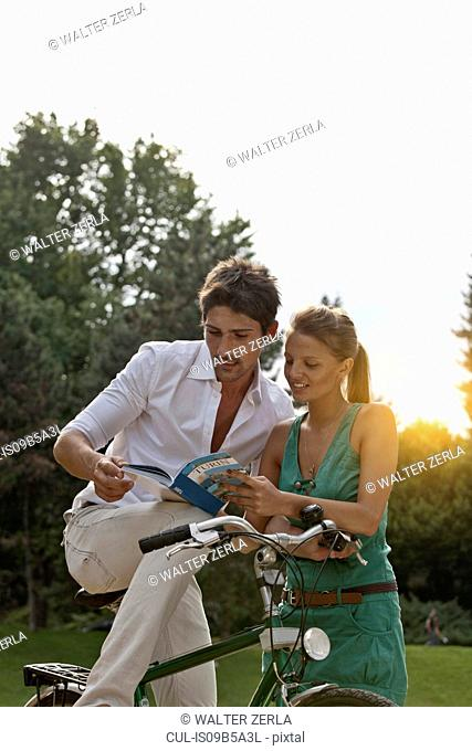 Young couple sitting on bicycle, looking at guidebook, Turin, Piedmont, Italy