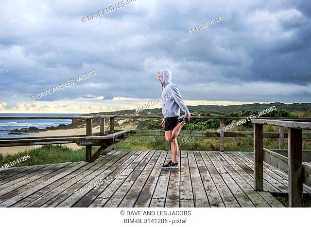 Caucasian runner stretching on wooden boardwalk by beach