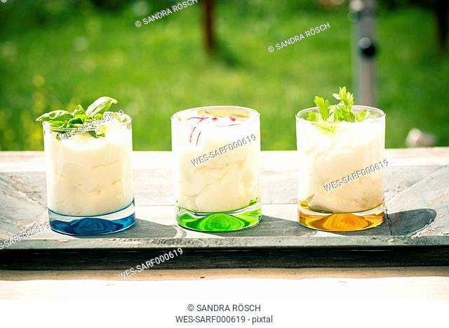 Three garnished glasses of curd with herbs on wooden tray