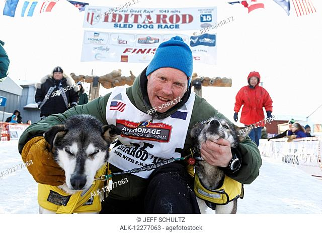Mats Pettersson hugs his lead dogs at the finish line in Nome during Iditarod 2015