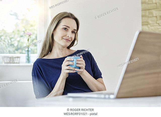 Woman at home with coffee mug and laptop