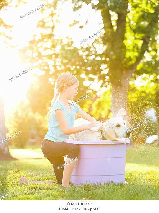 Caucasian girl washing pet dog in backyard