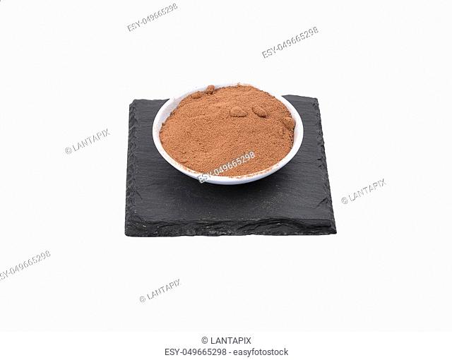 Bowl with cocoa powder on shale and white