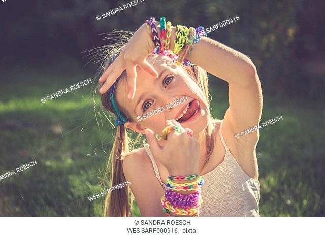 Portrait of little girl with outstretched tongue showing her loom bracelets and rings