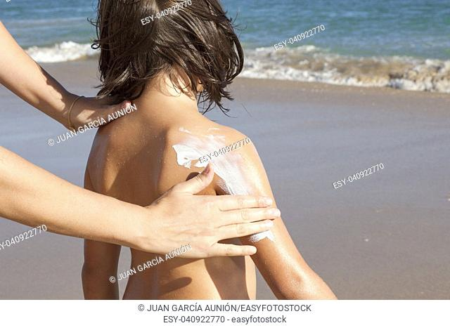Mother applying sunblock cream to her daughter on arm. Idyllic beach background