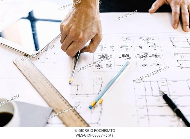 Architect working on construction plan, close-up
