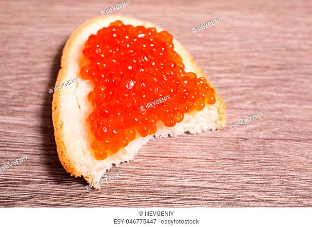Red caviar on a sandwich on the table. Healthy food. Fish appetizer. Russian kitchen. Space for the design, for the text