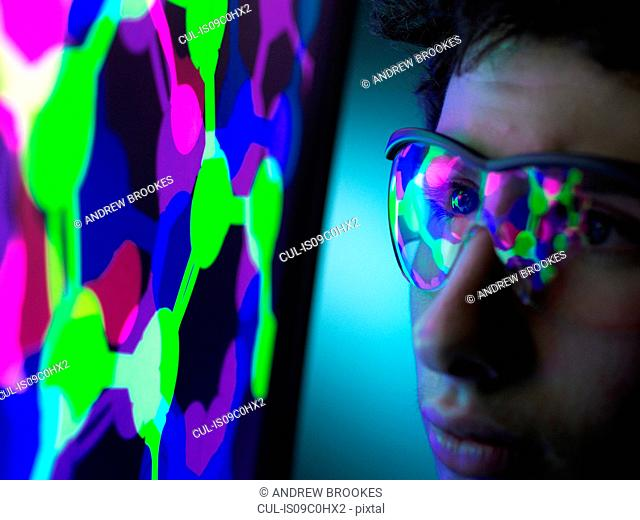Student understanding the design of a molecular structure on computer screen in laboratory