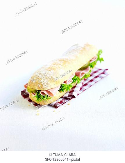 A sandwich with ham, lettuce and pickled gherkins