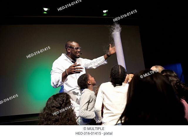 Children watching scientist demonstrating liquid nitrogen cloud in science center theater