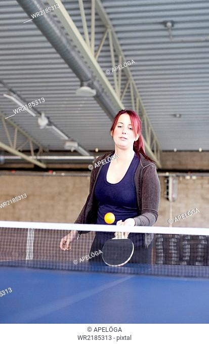 Young woman playing table tennis in fitness club