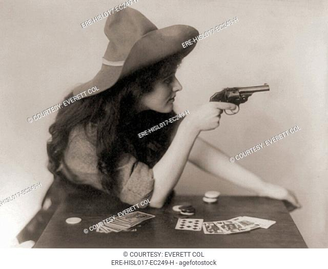 Cowgirl with deck of cards and chips, pointing a pistol. 1912