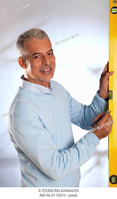 Architect man engineer holding using spirit level