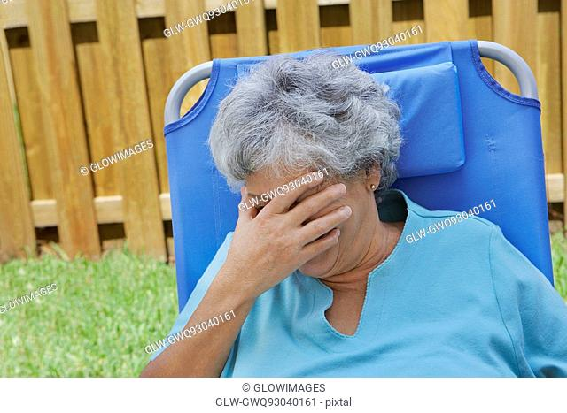Close-up of a senior woman covering her eyes with her hand