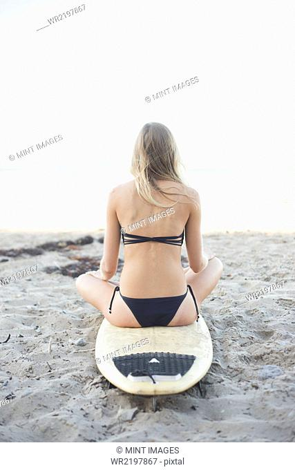 Blond woman in a black bikini sitting on a surfboard on a sandy beach