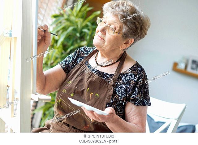 Senior adult woman painting on easel
