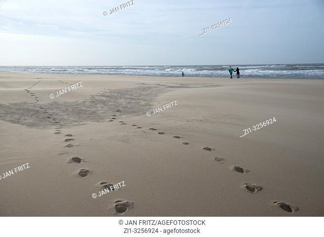 people and steps in the sand on a beach in Holland in a storm