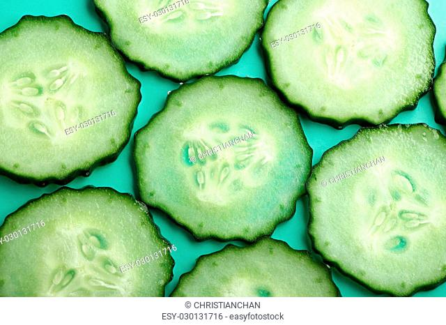 Sliced cucumber is on the green background
