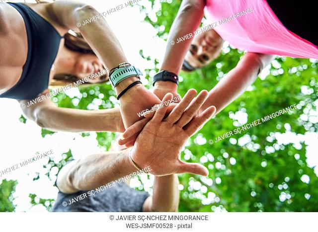 Young sports team stacking hands, celebrating success