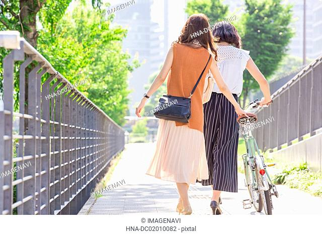A woman walking her bicycle and the other woman walking