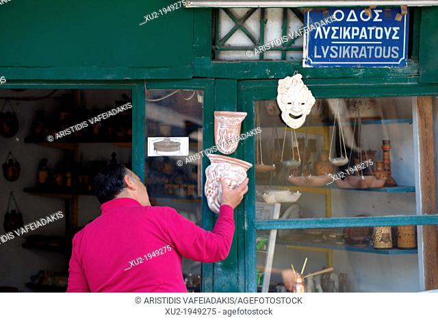 A man open his souvenir shop with theatrical masks in old district of Athens, Plaka