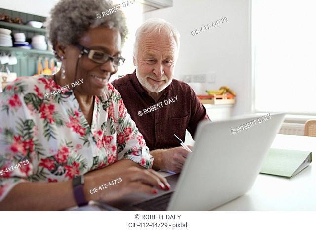 Senior couple paying bills at laptop in kitchen