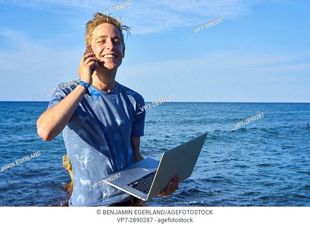 happy young man using mobile phone and laptop computer next to sea in holiday location Hersonissos, Crete, Greece