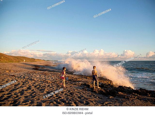 Boy and sister watching splashing waves from beach, Blowing Rocks Preserve, Jupiter Island, Florida, USA