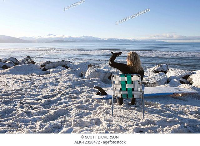 Female surfer relaxed in lawn chair on the snowy shore enjoying the view of Kachemak Bay, South-central Alaska; Homer, Alaska, United States of America