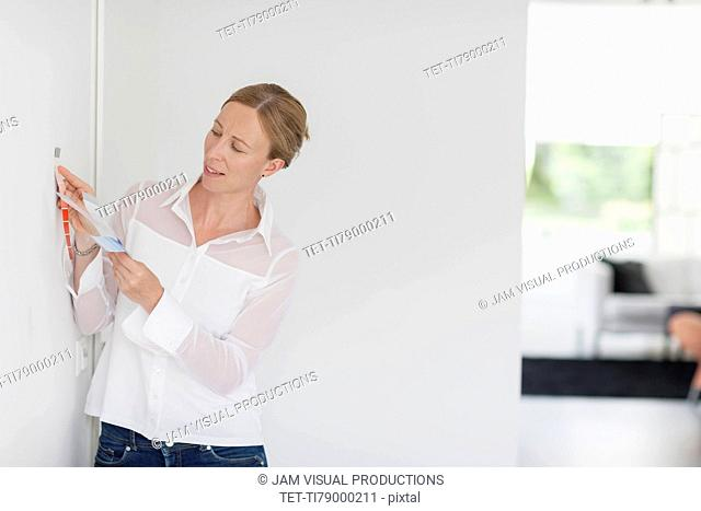 Woman comparing color swatch with white wall