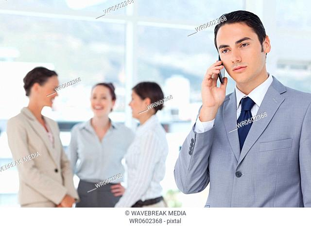 Businessman on his cellphone with colleagues behind him