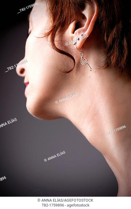 neck detail and profile of young woman with short hair and red and pending musical clef