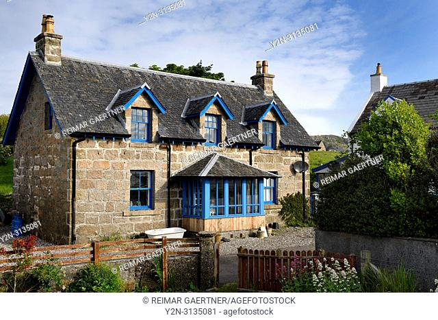 Stone house with blue trim and flower garden on main street of Baile Mor village on Isle of Iona Inner Hebrides Scotland UK