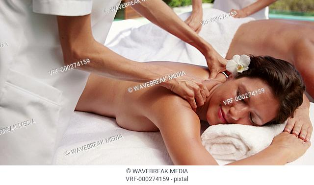 Couple getting massages by beauty therapists