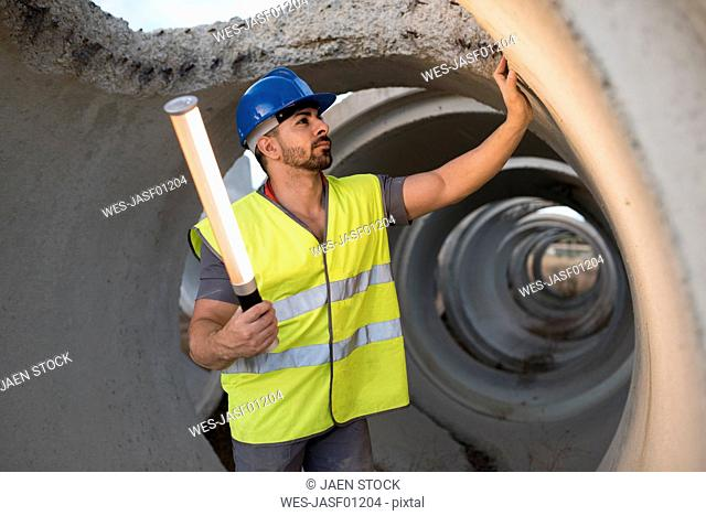 Construction worker examining concrete pipes