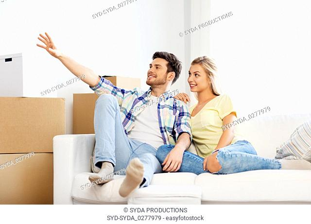 happy couple with cardboard boxes at new home