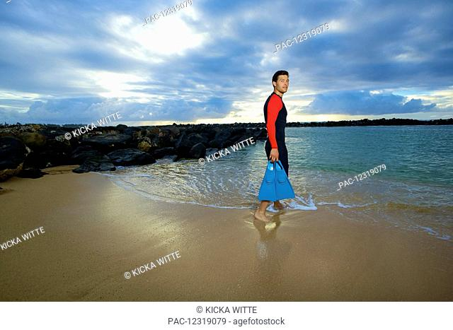 A man walks into the water from Lydgate Beach holding flippers; Kauai, Hawaii, United States of America