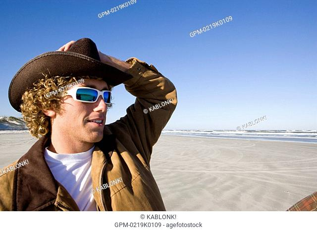 Close-up pf young man wearing sunglasses and cowboy hat at beach