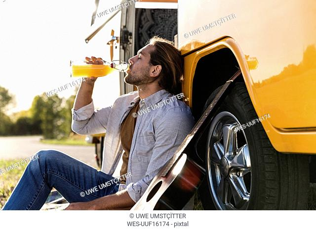 Young man on a road trip with her camper, taking a break, drinking juice
