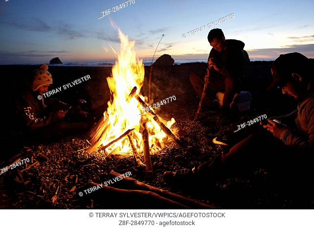Trevor Avery of the Yurok Indian Tribe, Anthony Henry, and Lonnie Risen Jr. , of the Hoopa Valley Tribe (from left) sit by a driftwood campfire while fishing...
