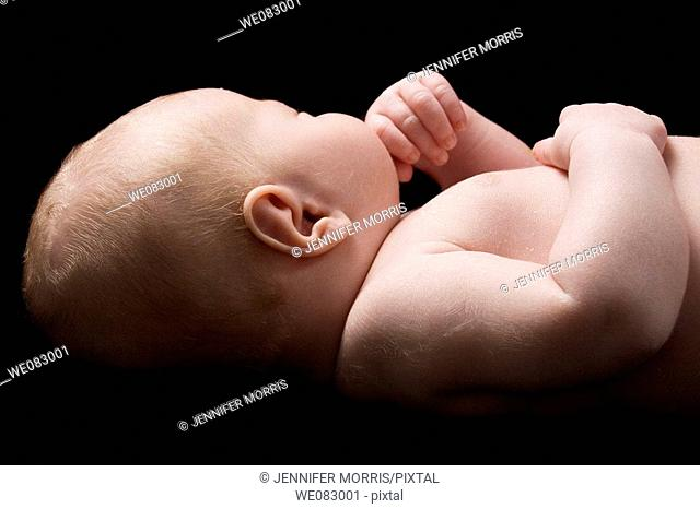 A fair-haired newborn baby with downy shoulders and flaking skin lies with his face turned away from the camera